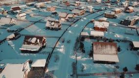 Levantamiento para arriba sobre el suburbio típico del invierno rodeado por la nieve clara blanca en la puesta del sol almacen de video