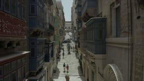 Levantamiento vertical, abejón que vuela la calle vieja hermosa estrecha, La Valeta, Malta Viejo, ventanas del vintage, balcones, almacen de metraje de vídeo