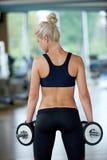 Levantando alguns pesos e trabalho em seu bíceps em um gym Foto de Stock