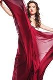 Levantando a mulher no vôo vermelho do vestido no vento Fotos de Stock Royalty Free