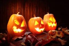 Levante la cara de la calabaza de Halloween de las linternas de o en fondo de madera Foto de archivo