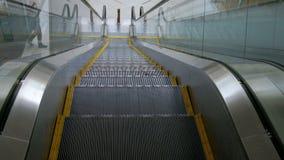 Levante la escalera móvil El individuo debajo de paseos cerca Una mirada real del hombre al movimiento de las escaleras Tiroteo d almacen de metraje de vídeo