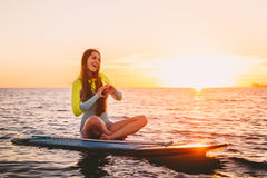 Levante-se o embarque da pá em um mar quieto com cores mornas do por do sol do verão Menina de sorriso feliz a bordo no por do so Imagens de Stock