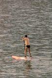 Levante-se o homem da placa de pá que paddleboarding Modelo masculino caucasiano novo na praia de Copacabana no trave das férias  fotografia de stock royalty free