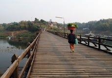 Levar da mulher bom em sua cabeça ao andar através de uma ponte de madeira fotos de stock royalty free