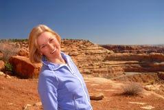 Levarsi in piedi sorridente della bella donna su una montagna Fotografia Stock