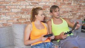Leve di comando emozionali del gioco della donna e dell'uomo nella console, fanno concorrenza e fanno i fronti divertenti pazzi 4 stock footage