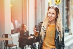 Leve embora o café Mulher urbana nova bonita que veste na roupa à moda que guarda o copo de café e que sorri ao andar fotografia de stock