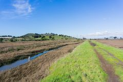 Levee in Don Edwards wildlife refuge, Coyote Hills Regional Park in the background, Fremont, San Francisco bay area, California stock photo