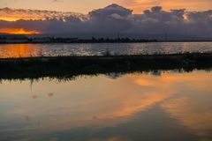 Levee and ponds in south San Francisco bay at sunset, Sunnyvale, California. Levee and ponds in south San Francisco bay at sunset, dark clouds in the background Royalty Free Stock Photos