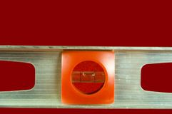 Level. A level tool set against a red background Stock Image