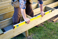Is it level?. Carpenter checking level of deck boards Royalty Free Stock Photography