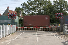 Level crossing lights and barrier with container train Stock Photos
