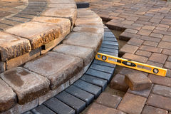 Level on pavers. Pavers meets with patio steps and job completion almost done, last check with yellow level Royalty Free Stock Photo