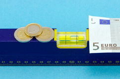 Level tool euro banknote coin on blue Royalty Free Stock Image