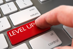 Level Up - Metallic Keyboard Concept. Hand Pushing Level Up Red Modern Laptop Keyboard Key. Laptop Keyboard with Level Up Red Button. Finger Pushing Level Up Royalty Free Stock Photography