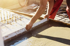 Leveling wet concrete surface with a metal screed board Stock Photography