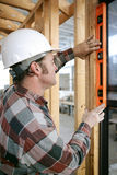 Leveling Window Vertical. A construction worker checking that a newly installed window is level.  Vertical view.  Authentic and accurate content Royalty Free Stock Image
