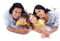 Levendige familie die op de vloer ligt Stock Afbeeldingen