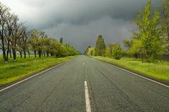 Levendige mening met weg en bewolkte hemel Stock Afbeeldingen