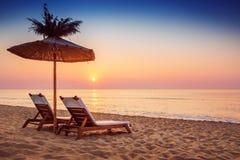 Levendige zonsopgang op een mooi zandig strand en een zonnescherm Royalty-vrije Stock Afbeeldingen
