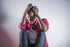 Levensstijl binnen portret van het jonge droevige en gedeprimeerde zwarte de zittings thuis vloer van de afro Amerikaanse vrouw w royalty-vrije stock foto