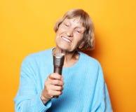 Levensstijl en mensenconcept: Het gelukkige oude hogere vrouw zingen met microfoon, die pret hebben, die muzikaal talent uitdrukk royalty-vrije stock foto