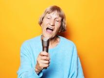 Levensstijl en mensenconcept: Het gelukkige oude hogere vrouw zingen met microfoon, die pret hebben, die muzikaal talent uitdrukk stock afbeeldingen