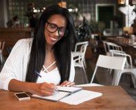 Levensstijl en mensenconcept: Het mooie Afrikaanse meisje maakt nota's in cafetaria Stock Afbeelding