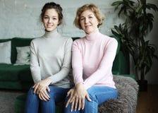 Levensstijl, familie en mensenconcept: Gelukkige jonge vrouw en haar moeder thuis stock afbeelding