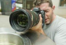 Levensstijl grappig portret van de jonge die mens van de paparazzifotograaf in actie achter stadsdocument mand het besluipen voor royalty-vrije stock afbeelding