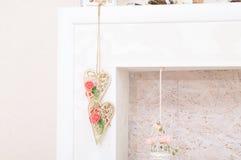 Levensstijl met houten harten met witte en roze bloemen in open haard voor weelderig binnenland Weinig die lijst met kaarslicht,  Royalty-vrije Stock Fotografie