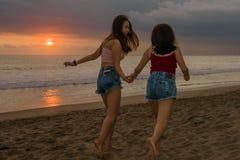 Levensstijl in openlucht portret van twee jonge zusters of Aziatisch Chinees meisje bij zonsondergangstrand met haar beste vriend stock foto's