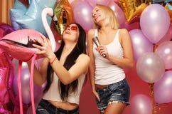 Levensstijl, partij en mensenconcept: Gelukkige meisjes met microphon Stock Fotografie