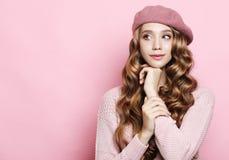 Levensstijl, schoonheid en mensenconcept: Schoonheidsmeisje met krullend perfect kapsel die roze baret over witte achtergrond dra royalty-vrije stock foto
