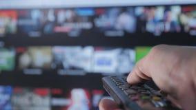 Levensstijl slimme TV De online video stromende dienst met apps en hand Mannelijke hand die de controledraai ver weg houden stock videobeelden