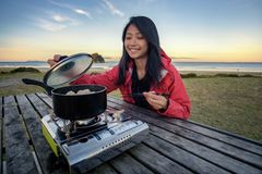 Levensstijlbeeld van jonge gelukkige Aziatische vrouw die heet pottenfornuis op een lijst openlucht langs strand eten Het beeld v stock fotografie