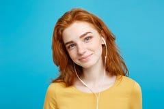 Levensstijlconcept - het Portret van het vrolijke gelukkige meisje van het gember rode haar geniet van luister aan muziek met bli royalty-vrije stock afbeeldingen