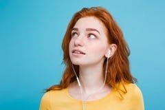 Levensstijlconcept - het Portret van het vrolijke gelukkige meisje van het gember rode haar geniet van luister aan muziek met bli stock foto's