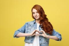 Levensstijlconcept: Mooie aantrekkelijke vrouw die in denim een hartsymbool met haar handen maken stock afbeeldingen