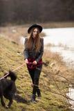 Levensstijlportret die van jonge vrouw in zwarte hoed met haar hond, door het meer op een aardige en warme de herfstdag lopen stock afbeelding