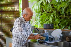 levensstijlportret van de hogere gelukkige en zoete Aziatische Japanse teruggetrokken mens die thuis keurige alleen keuken koken royalty-vrije stock afbeeldingen