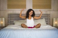 Levensstijlportret van de jonge mooie en gelukkige Latijns-Amerikaanse slaapkamer van vrouwenontwaken thuis in de ochtend het uit royalty-vrije stock foto's