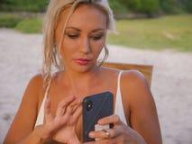 Levensstijlportret van jonge aantrekkelijke en ontspannen blonde vrouw die mobiele telefoon Internet die app met behulp van of vo stock foto's