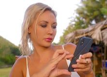 Levensstijlportret van jonge aantrekkelijke en ontspannen blonde vrouw die mobiele telefoon Internet die app met behulp van of vo royalty-vrije stock afbeelding
