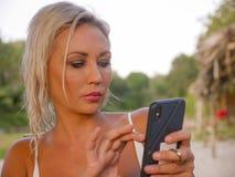 Levensstijlportret van jonge aantrekkelijke en ontspannen blonde vrouw die mobiele telefoon Internet die app met behulp van of vo royalty-vrije stock foto