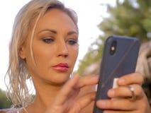 Levensstijlportret van jonge aantrekkelijke en ontspannen blonde vrouw die mobiele telefoon Internet die app met behulp van of vo royalty-vrije stock fotografie
