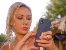 Levensstijlportret van jonge aantrekkelijke en ontspannen blonde vrouw die mobiele telefoon Internet die app met behulp van of vo stock foto