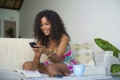 Levensstijlportret van jonge gelukkige en mooie Spaanse vrouw die thuis het mobiele die telefoon voorzien van een netwerk en text stock afbeeldingen