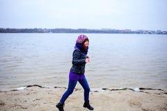 Levensstijlportret van jonge Kaukasische slanke vrouwenlooppas langs de strandherfst Royalty-vrije Stock Afbeeldingen